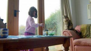 Autistisches Mädchen mit Schwierigkeiten malt in Gesellschaft ihrer Katze