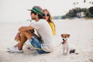 Paar am Strand genießt Augenblick mit Hund