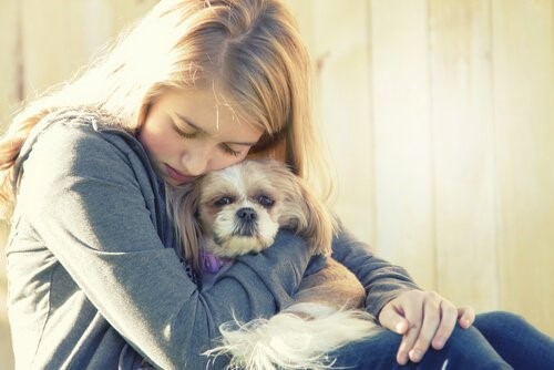 Depressionen bei Hunden - Mädchen umarmt Hund