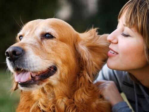 Frau flüstert ihrem Hund ins Ohr
